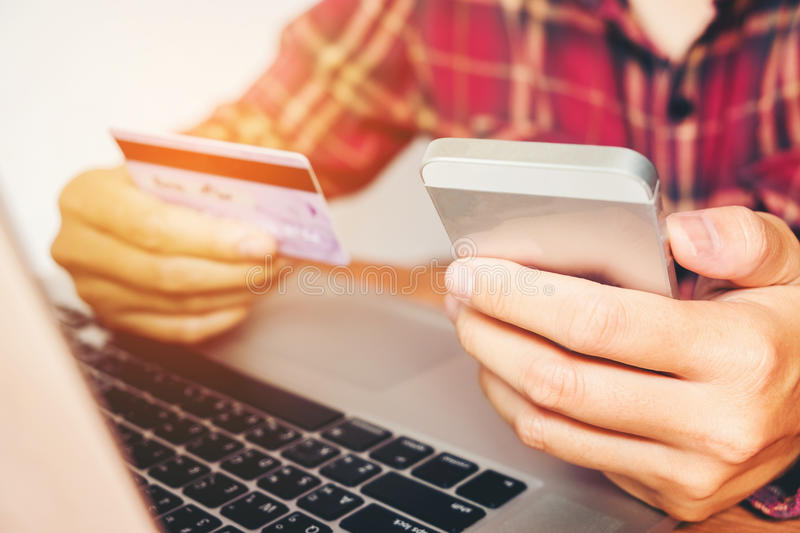 Man Holding Credit Card And Using Cell Phone holding credit card with shopping online.  stock photos
