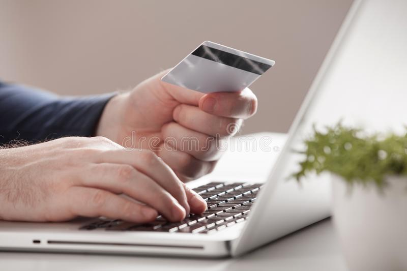Man holding credit card and using laptop. Online shopping concept royalty free stock photos