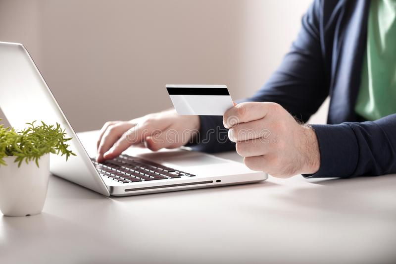 Man holding credit card and using laptop. Online shopping concept royalty free stock image