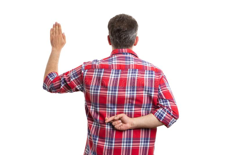 Man holding crossed fingers behind back as fake oath royalty free stock photos