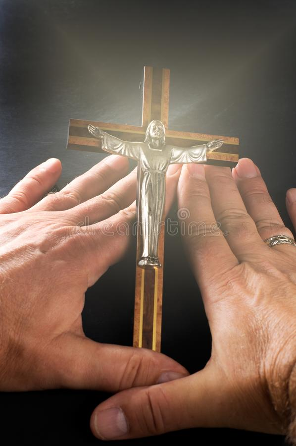 Man Holding a Crucifix with Divine Light royalty free stock photography