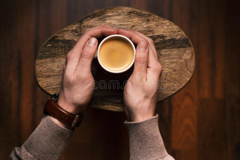 Man holding a cup of coffee on a wooden, vintage background. Hand of young businessman holding a mug of coffee. Vintage tones. royalty free stock photos