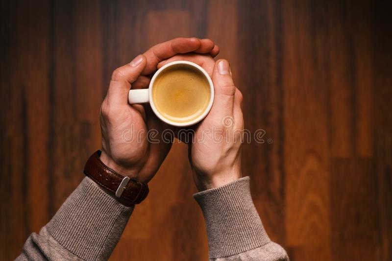 Man holding a cup of coffee on a wooden, vintage background. Hand of young businessman holding a mug of coffee. Vintage tones. royalty free stock image