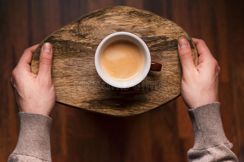Man holding a cup of coffee on a wooden, vintage background. Hand of young businessman holding a mug of coffee. Vintage tones. stock images