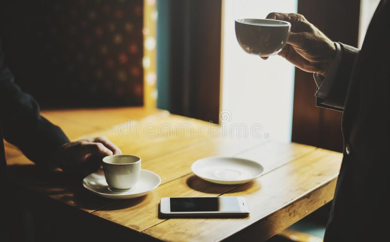Man Holding Cup Near Table royalty free stock photo