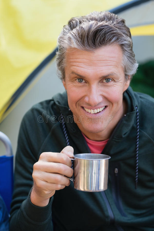 Man holding cup by tent at campsite. Portrait of man holding cup by tent at campsite stock images