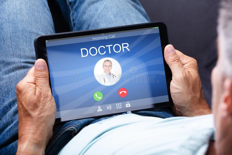 Man Holding Digital Tablet With Doctor`s Call On Display stock photo