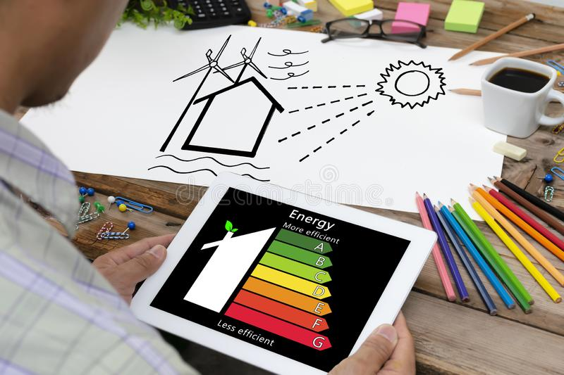 Man holding digital tablet and looking at house efficiency rating stock photo