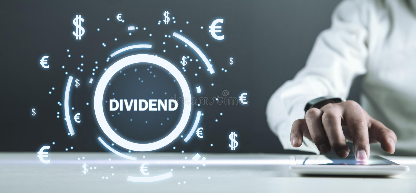 Man holding Dividend text with currency symbols. Business stock photography
