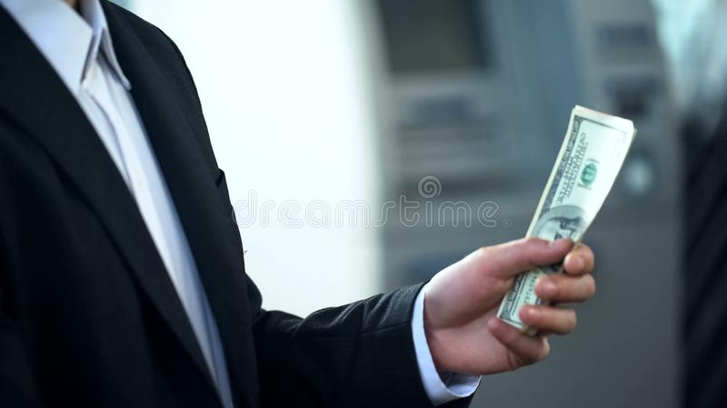 Man holding dollars banknotes withdrawn from ATM, good service, business trip. Stock photo stock photos