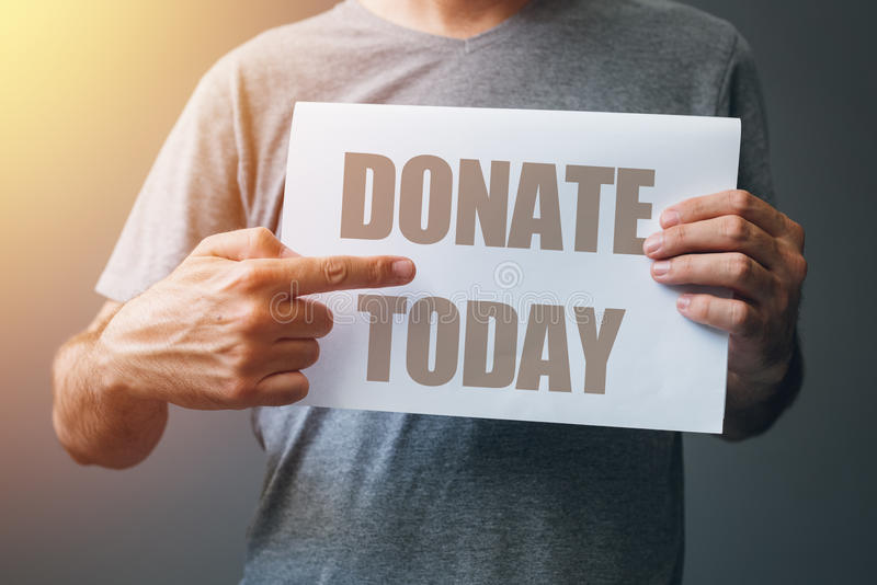 Man holding Donate today poster. Finger pointing to text stock photo