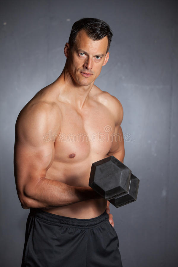 Man holding a dumbbell doing a fitness workout stock image