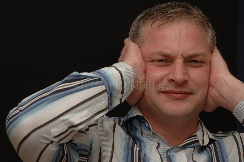 Man Holding Ears. A middle aged man with an annoyed expression holds his hands over his ears as if to block out a loud noise stock image