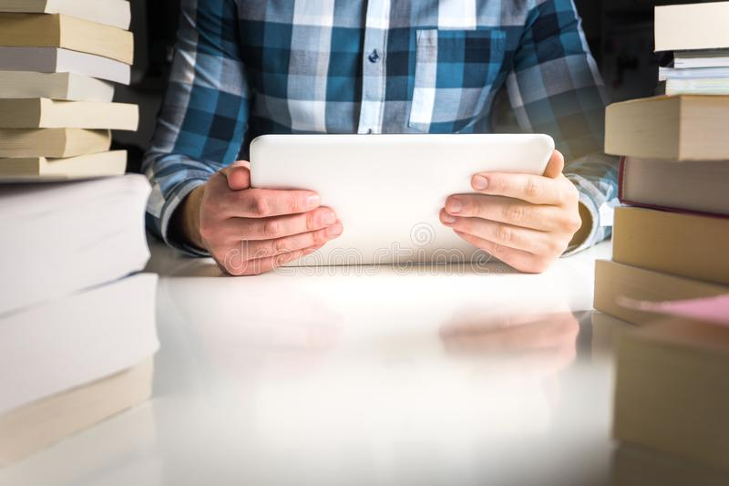 Man holding electronic book reader. Student reading book with tablet and smart mobile device in library or home royalty free stock photo