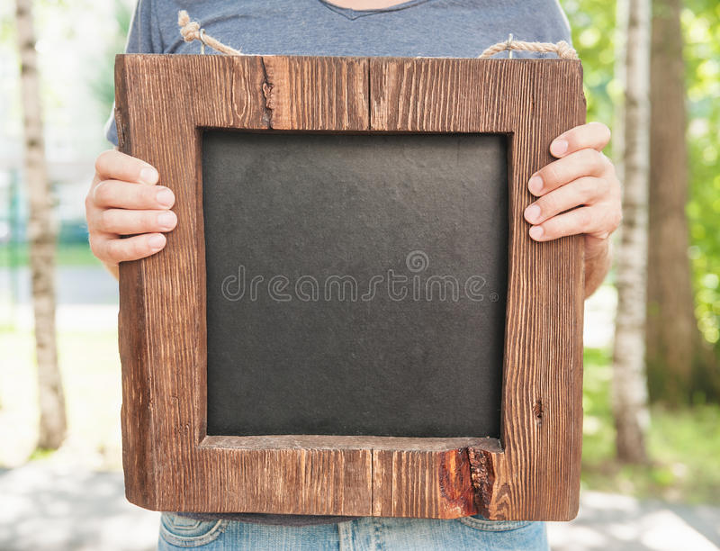 Man holding empty wooden and slate board. Template Mock up royalty free stock photos