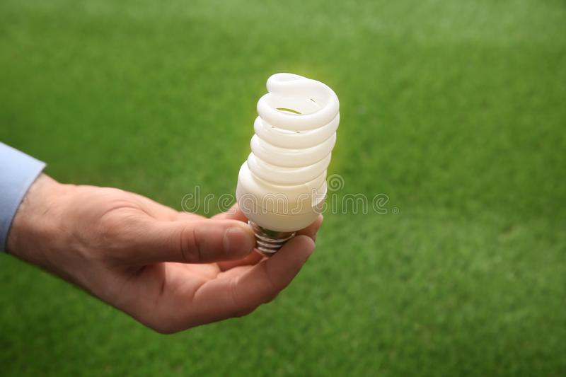 Man holding energy saving bulb for lamp against green grass royalty free stock photo