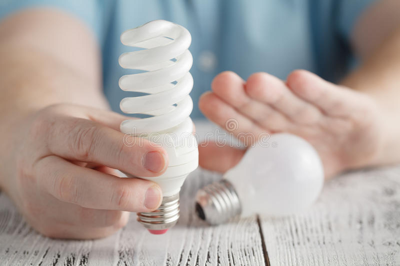 Man holding an energy saving lamp and refuse normal light bulb royalty free stock photos