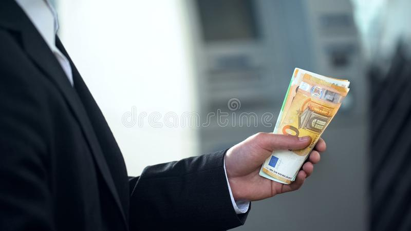Man holding euro banknotes withdrawn from ATM, good service, business trip stock image
