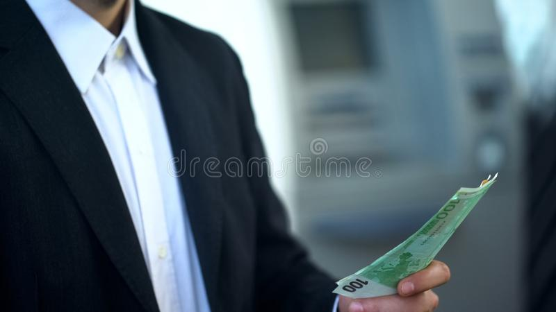 Man holding euros just withdrawn from ATM, good service, business trip to Europe. Stock photo royalty free stock photo