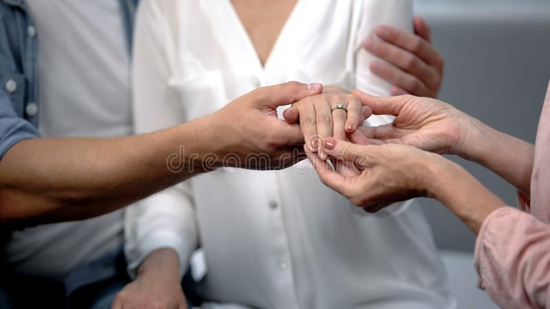 Man holding fiancee hand with engagement ring, showing to mother, happy family. Stock photo stock images