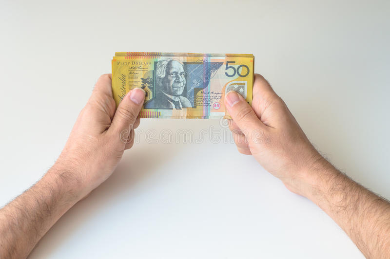 Man holding fifty Australian Dollar banknote. In his hands stock image