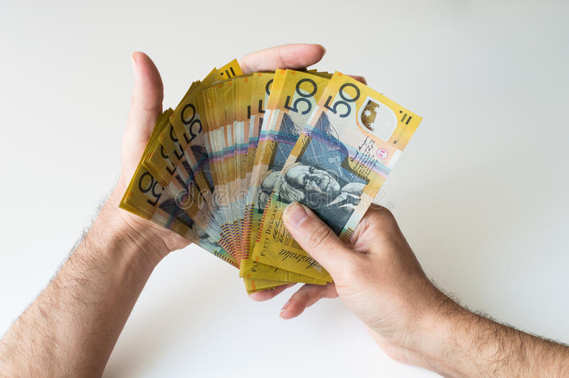 Man holding fifty Australian Dollar banknote. In his hands stock photography