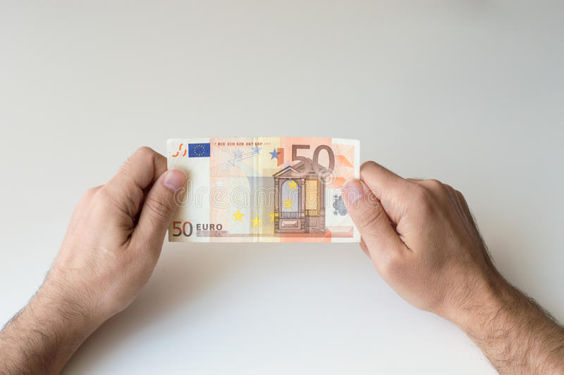 Man holding fifty Euro banknote. In his hands stock photography