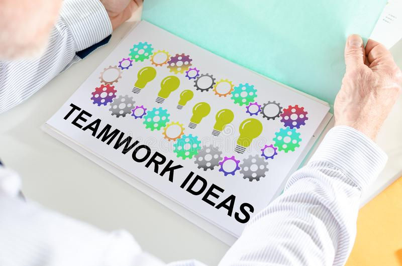 Teamwork idea concept on a paper. Man holding a file with teamwork idea concept stock photo