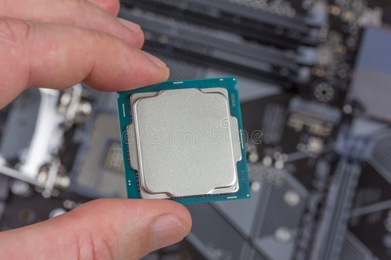 Man holding fingers mock up desktop processor 8th gen on background motherboard closeup royalty free stock photo