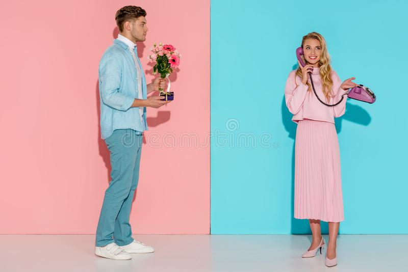 Man holding flower bouquet and gift box while smiling woman talking on vintage telephone. With pink and blue background royalty free stock image
