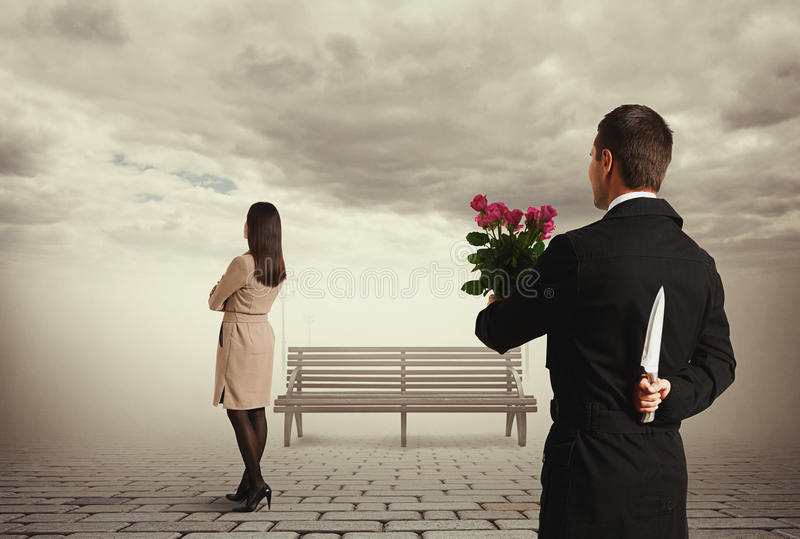 Man holding flowers and knife behind back stock photography