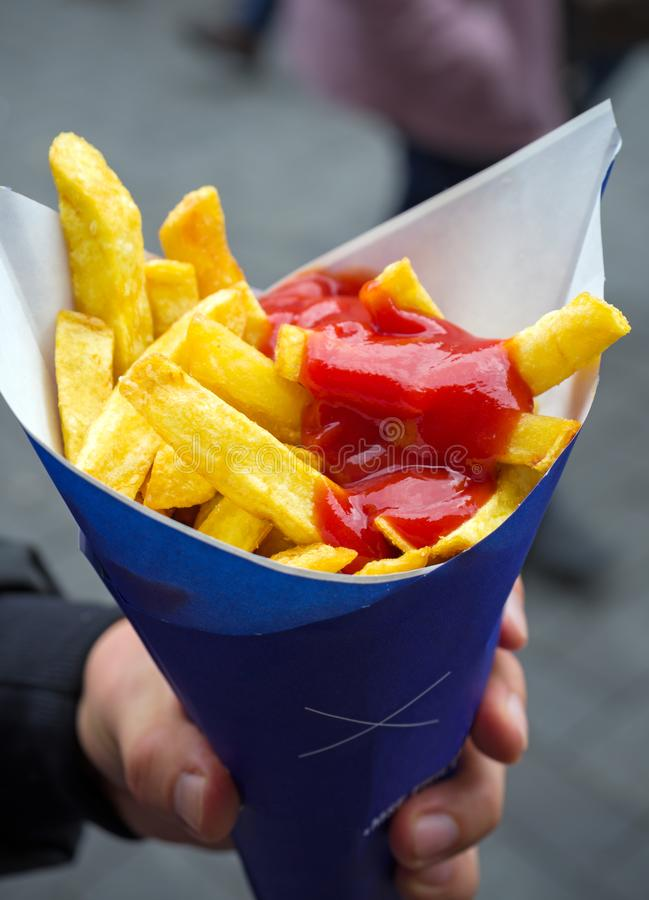 Man holding French fries in paper cornet with ketchup. Street food royalty free stock photos