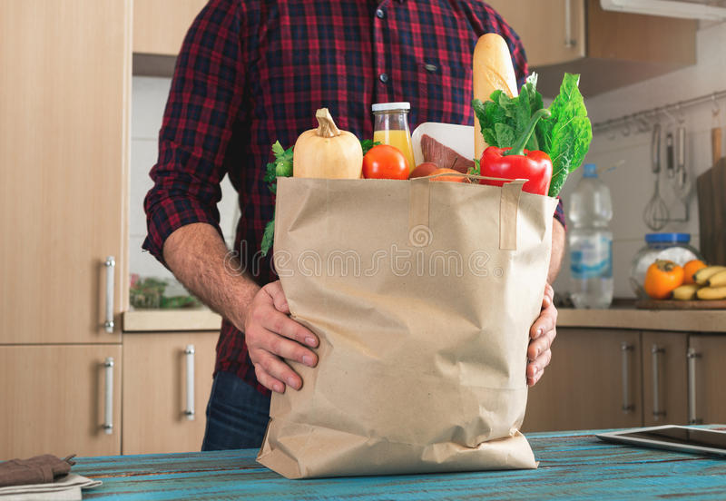 Man holding full paper bag of healthy food. On a wooden table in the home kitchen close up royalty free stock photo