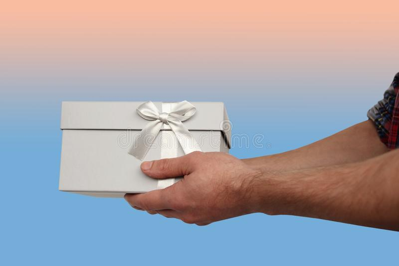 Man holding a gift in a light gray box with a satin ribbon and a bow, the concept of Valentine`s Day, Christmas presents, mother royalty free stock photo