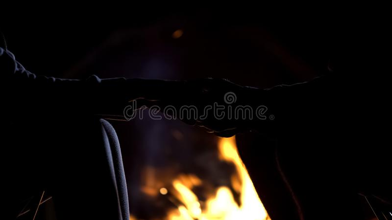 Man holding girlfriends hand against bonfire, romantic love confession, night royalty free stock photos