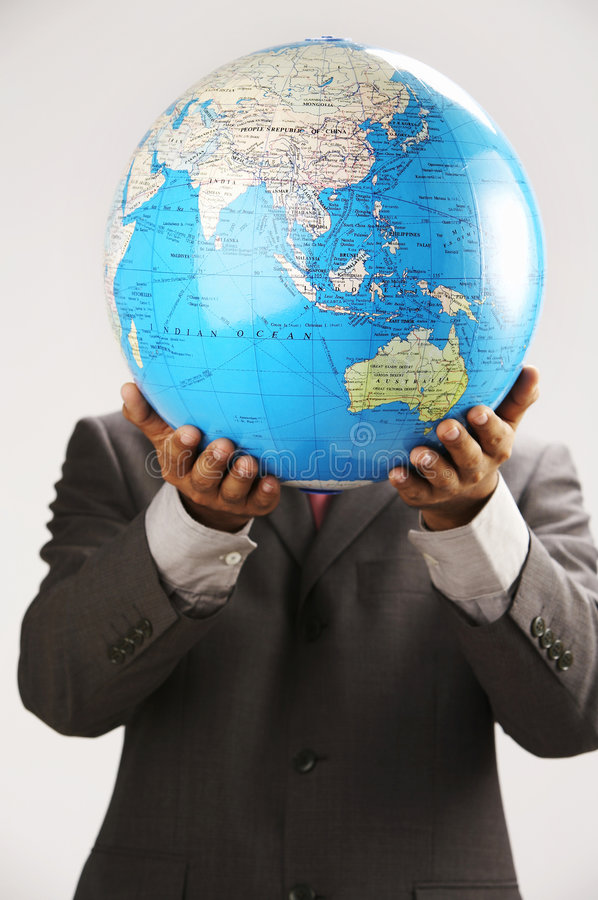 Man holding globe over face. Businessman holding globe over face royalty free stock photography