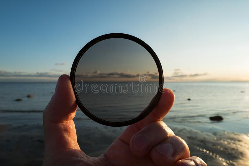Man holding gradient neutral density ND filter on background of summer sunset royalty free stock images