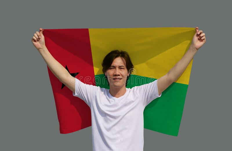The man holding Guinea Bissau flag in his hands and raising to the end of the arm at the back on grey background. The man is holding Guinea Bissau flag in his stock photo