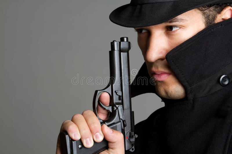 Man Holding Gun. Sneaky spy man holding gun royalty free stock photos