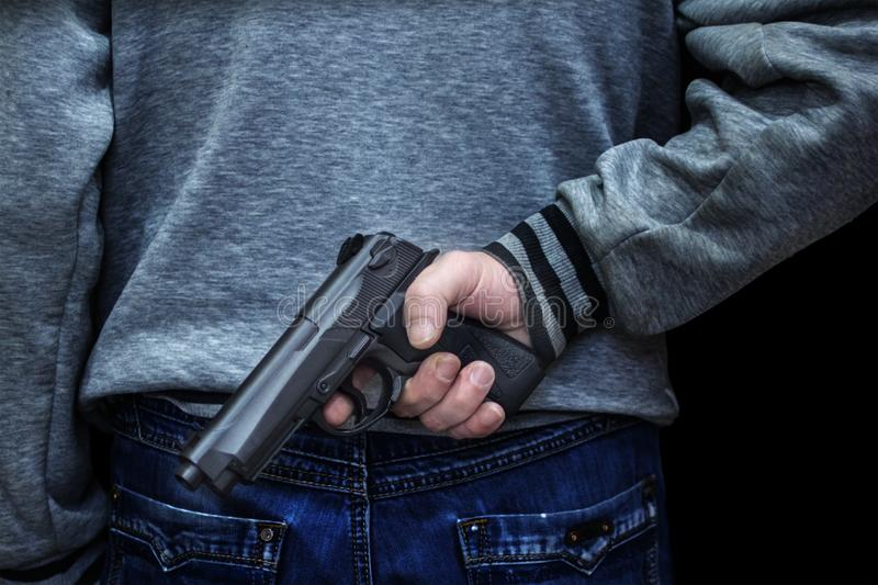 Man holding a gun behind his back against a black background. concept of danger, crime stock photography