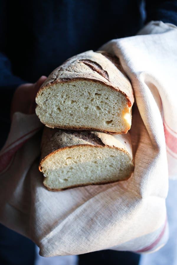 Halfed Homemade sourdough bread. A man holding a halfed homemade sourdough bread stock image