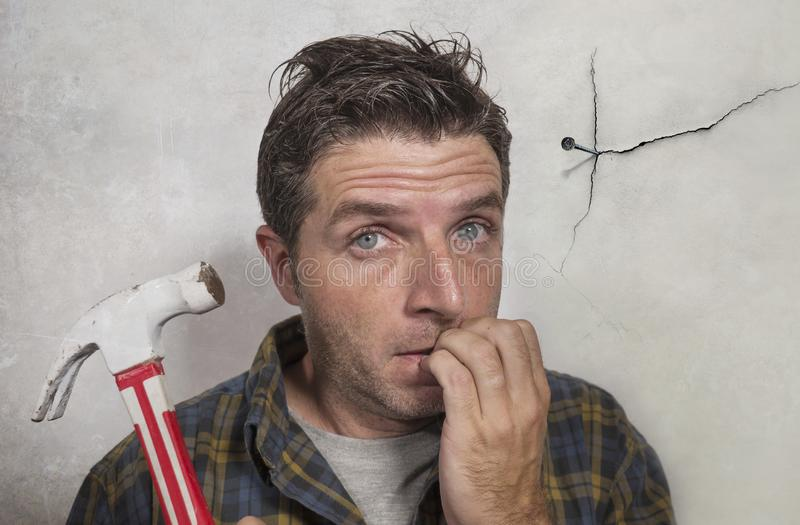 Man holding hammer driving a nail for hanging a frame but making funny faces for the  mess cracking the wall as a disaster DIY guy royalty free stock photography