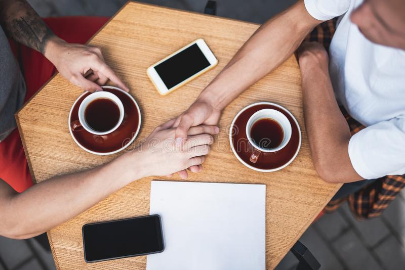 Man holding hand of friend at table. Top view close up male keeping hand of another guy. They sitting at table with cups of coffee and mobiles royalty free stock photography