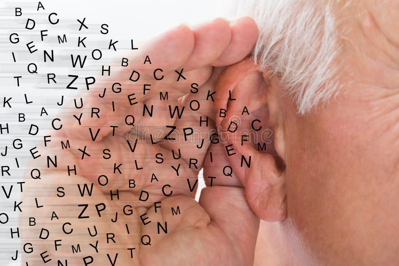 Man Holding Hand Near Ear And Listening Carefully. Mature Man Holding Hand Near Ear And Listening Carefully Alphabet Letters Fly royalty free stock photo