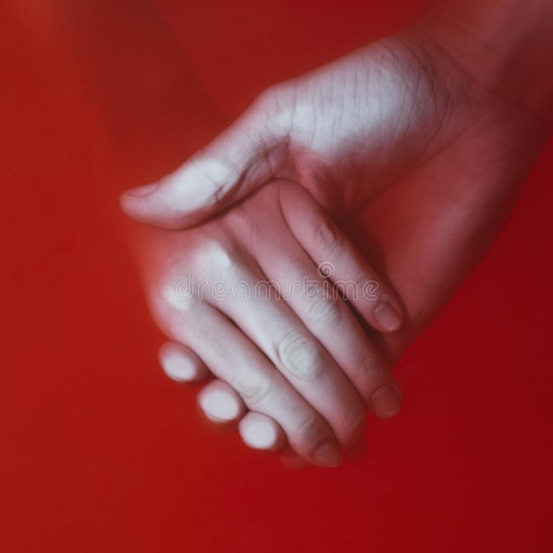 Man holding the hand of a woman in the red blood water, couple relationship, the concept of the price of love stock photography