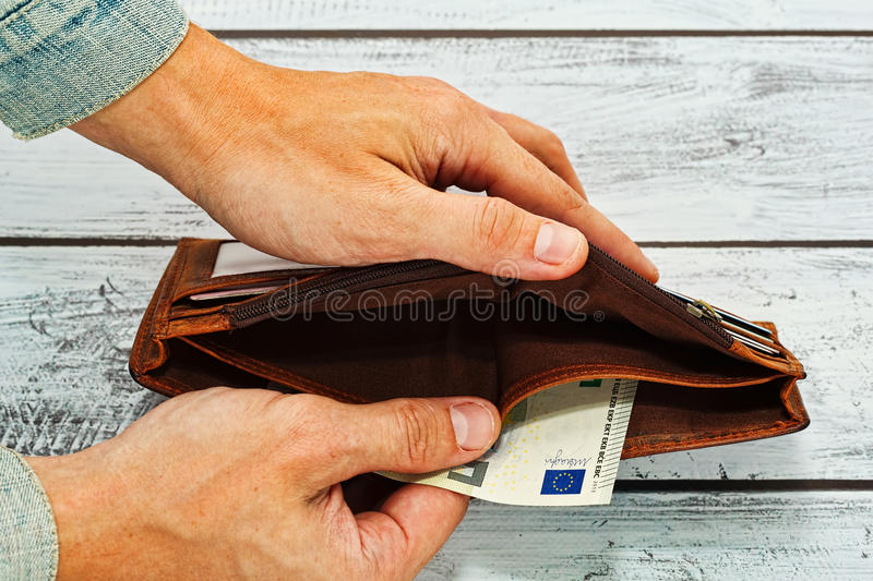Man holding in hands almost empty wallet royalty free stock photo
