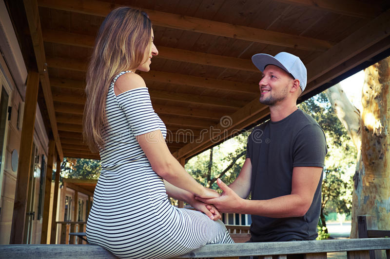 Man is holding hands of his wife during the romantic conversation on the terrace. Close-up of a handsome bearded men who is holding hands of his wife during the royalty free stock image
