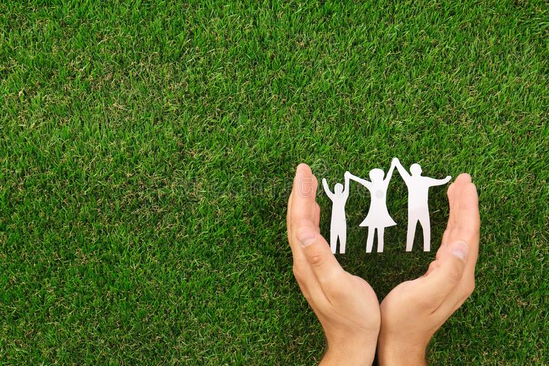 Man holding hands near paper silhouette of  on green grass, top view. Space for text. Man holding hands near paper silhouette of family on green grass, top view stock image