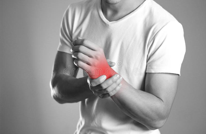 A man holding hands. Pain in the wrist. The hearth is highlighted in red. Close up. Isolated background.  royalty free stock images