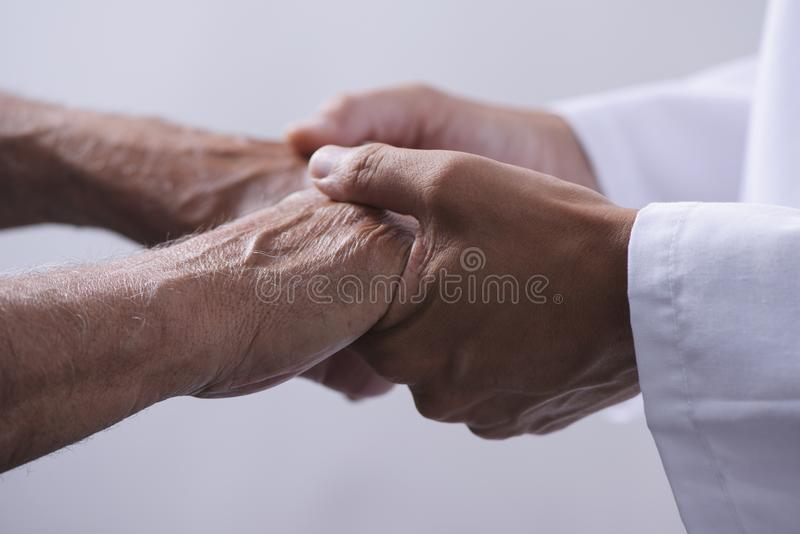 Man holding the hands of a senior man royalty free stock image